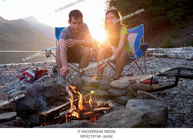Couple roasting hot dog on campfire