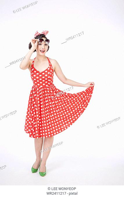Young smiling woman in retro style standing holding her skirt of dress looking over her sunglasses