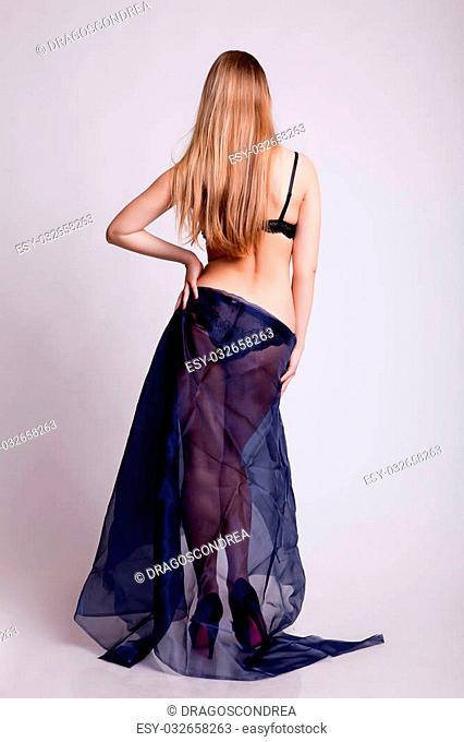 Sexy blonde posing with her buttocks at camera covered with blue cover. Posing sexual to the camera