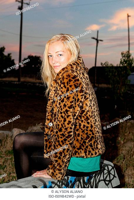 Portrait of young woman in leopard skin jacket at dusk
