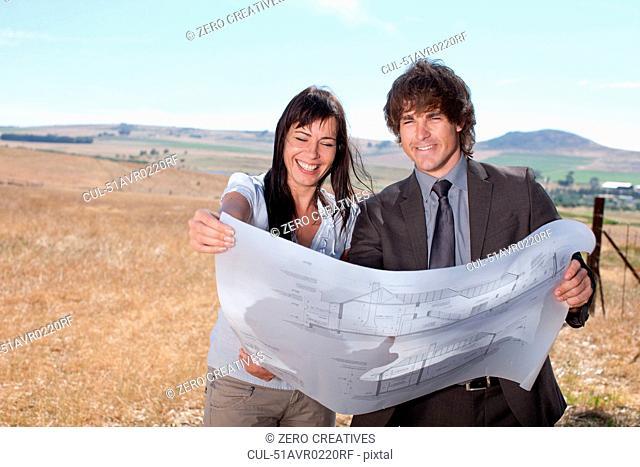 Business people reading blueprints
