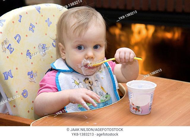 One year old dirty baby girl in high chair eating yogurt using spoon