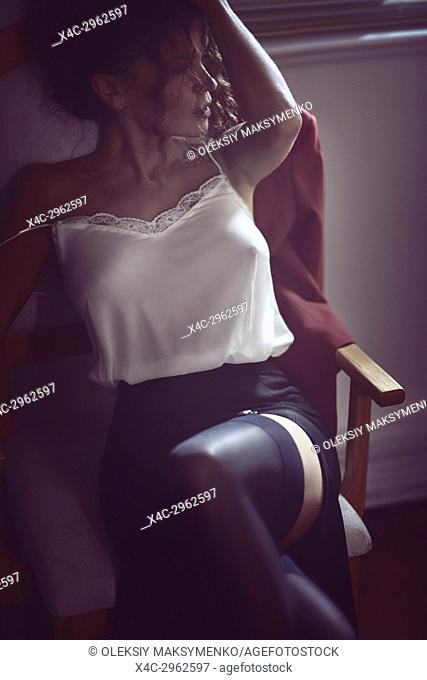 Beautiful sexy woman sitting in a chair half dressed in a night shirt and stockings in a dimly lit room