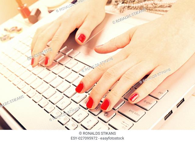 fashion woman with red polished nails working on laptop. writing blog concept