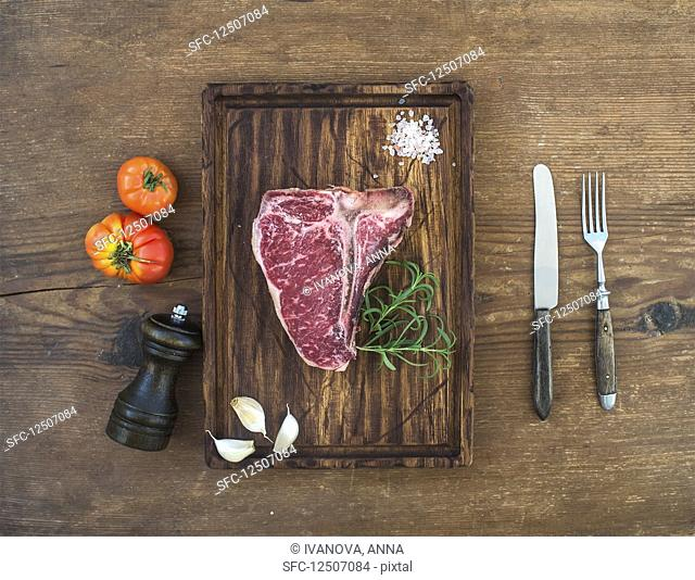Raw t-bone steak with garlic cloves, tomatoes, rosemary and salt