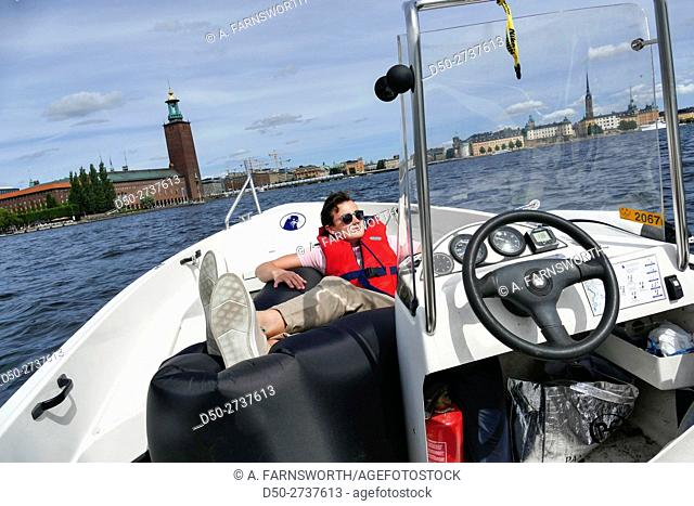 STOCKHOLM SWEDEN 15 year old relaxes in a blow-up Laybag in a boat in Riddarfjärden with the Stockholm City Hall in background