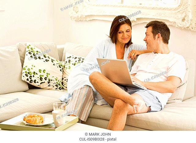 Mature couple on sofa browsing laptop and having breakfast