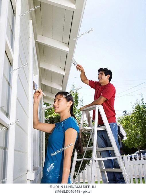 Multi-ethnic couple painting house