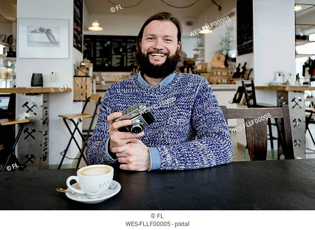 Man with beard sitting in cafe, holding old camera