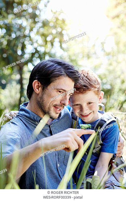 Father showing son a grasshopper