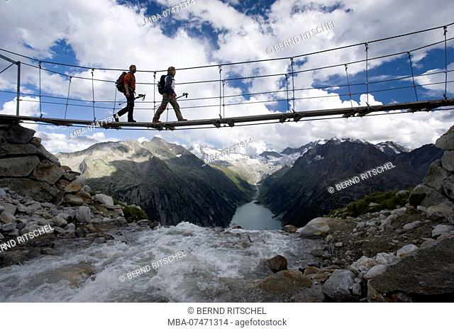 Hiking on the suspension bridge at the Olper hut and view of Schlegeisspeicher, Tuxer Alps, Zillertal, Tyrol, Austria