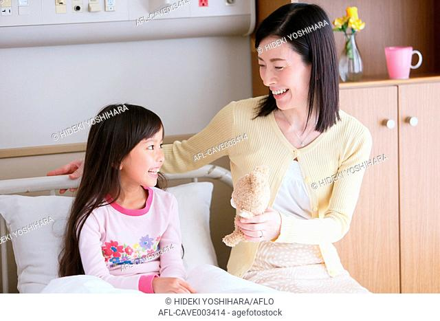 Sick young Japanese girl with mother at the hospital