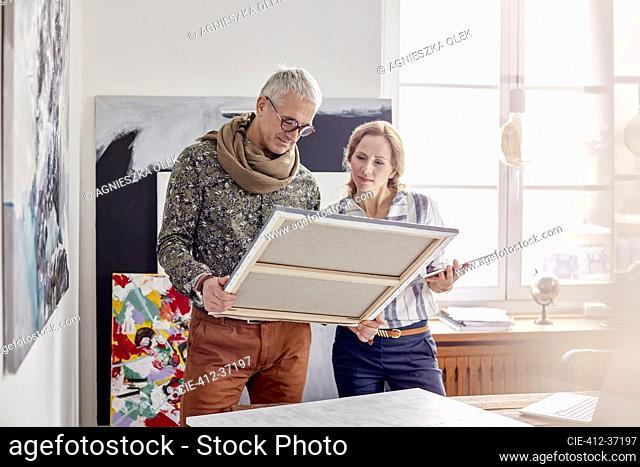 Painters examining painting in art studio