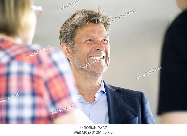 Smiling man in suit looking at couple