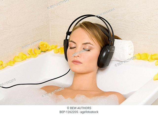 Young woman listening to music while taking bath