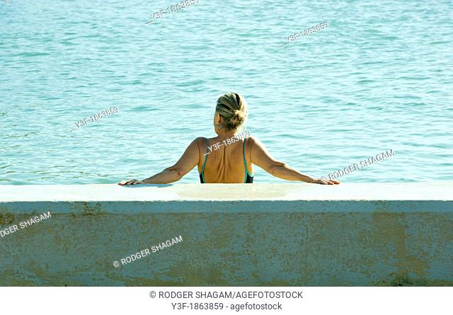 A woman rests against the wall of a tidal pool