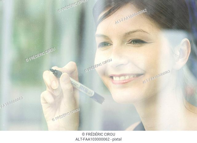 Woman preparing to write on window with marker