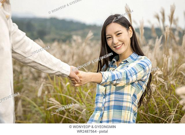Portrait of young smiling woman hand in hand with a man in silver grass field