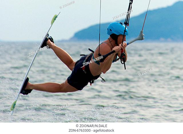 Close-up of female kite surfer while jumping