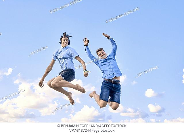 Two friends jumping against sky
