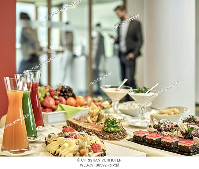 Buffet with appetizers and business people in background