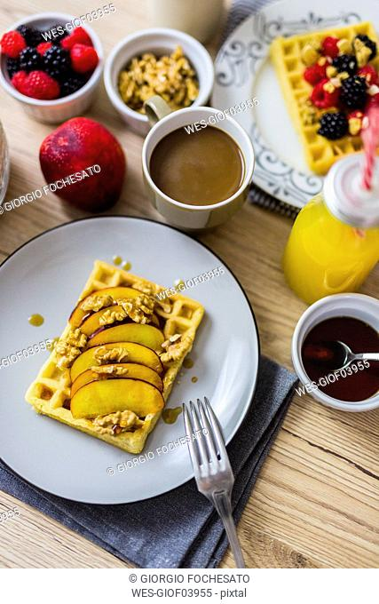 Breakfast table with waffle garnished with nectarine, walnuts and maple sirup