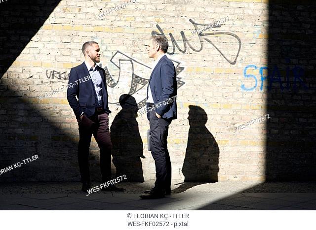 Two businessmen talking at graffiti wall