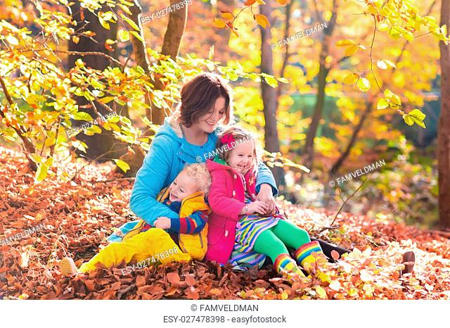 Mother and kids play in autumn park. Parent and children walk in the forest on a sunny fall day. Boy and girl playing outdoors with yellow maple leaf