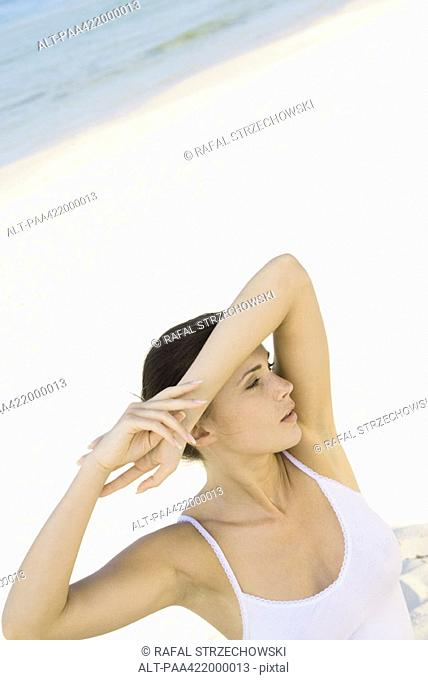 Woman on beach, shading eyes with arm