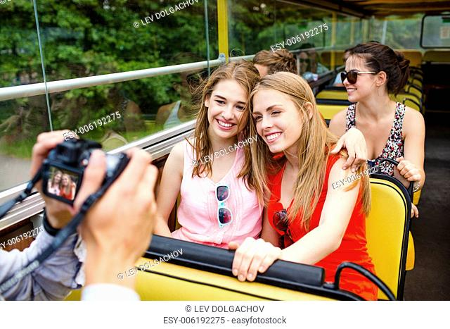 friendship, travel, vacation, summer and people concept - smiling friends with camera traveling by tour bus