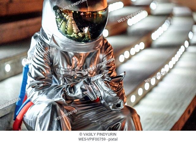 Spaceman sitting on illuminated stairs at night using cell phone