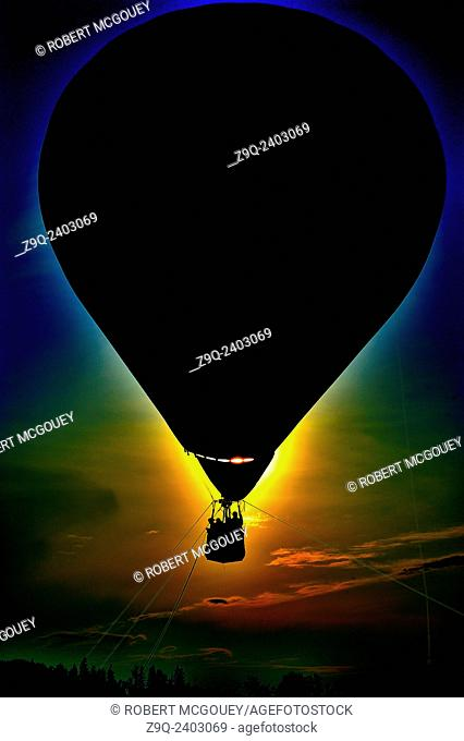 A hot air balloon silhouetted by the setting sun in southern Alberta Canada