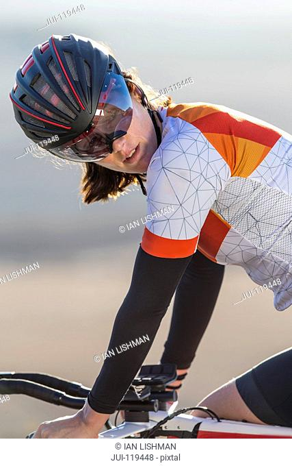 Close-up of female cyclist riding race bicycle on sunny open road