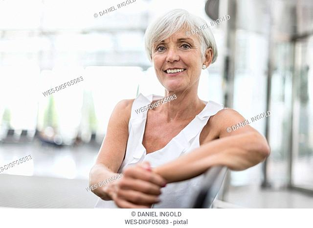 Portrait of smiling senior woman sitting in waiting area
