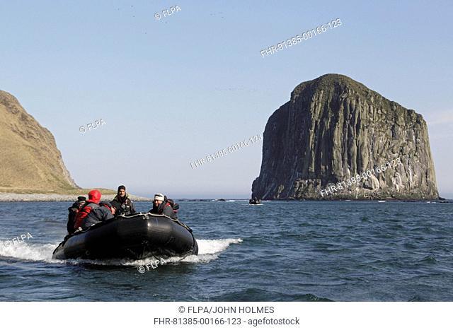 Zodiac inflatable boat with tourists at sea, Yankicha Island, Kuril Islands, Sea of Okhotsk, Sakhalin Oblast, Russian Far East, Russia, june