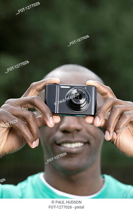 Man taking photograph with digital camera