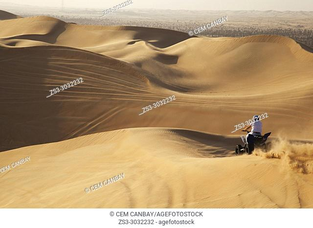 Motorcyclist riding in the sand dunes at desert landscape, Abu Dhabi, United Arab Emirates, Middle East