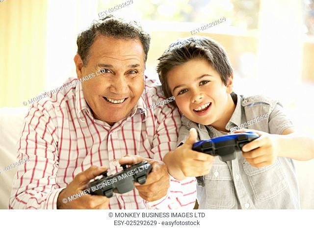 Hispanic Grandfather And Grandson Playing Video Game At Home