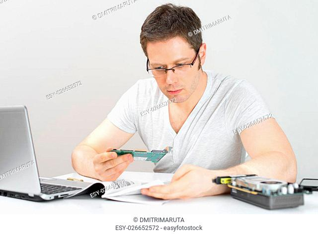 Male technician reading manual at his workplace