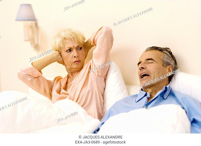 Senior woman holding ears while senior man snores in bed