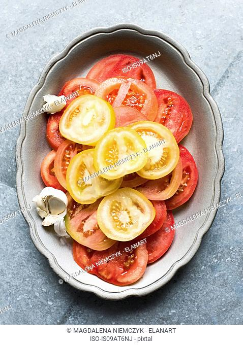 Still life of red and yellow sliced tomatoes in dish