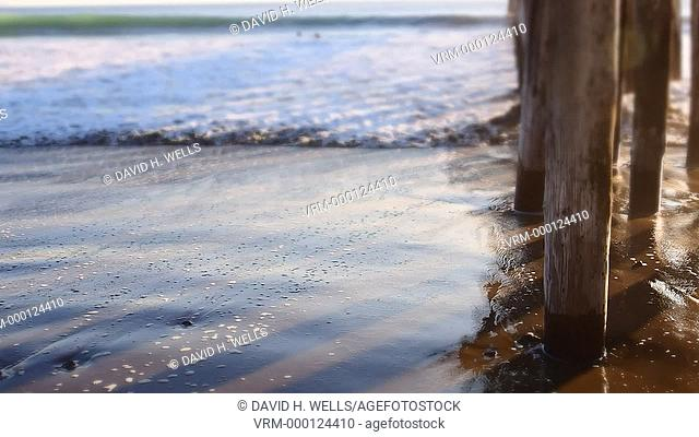 Ocean waves hitting the shore under the pier in Cayucos, California United States