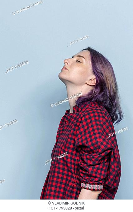 Side portrait of young woman with dyed hair and eyes closed against gray background