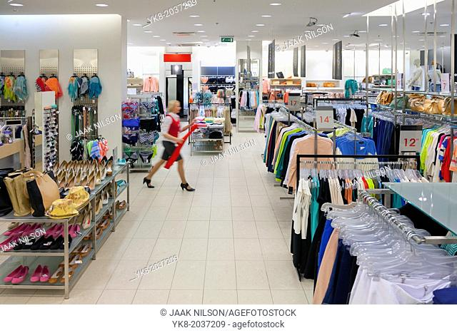 Woman, buyer walking in fashion shop aisle. Retail outlet and fashion shop interior. Shopping