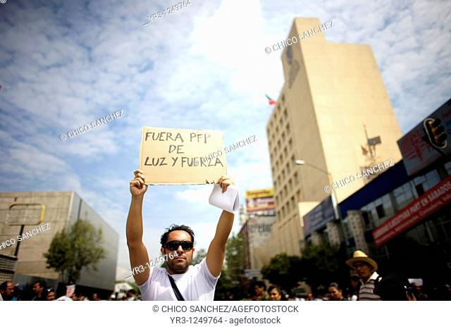 An electrician protests the government's shut down of state-run power company Luz y Fuerza del Centro LFC outside the LFC headquarters, right, in Mexico City