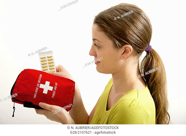 Young beautiful woman in yellow, holding a red first aid kit, and a blister of yellow tablets in her hand