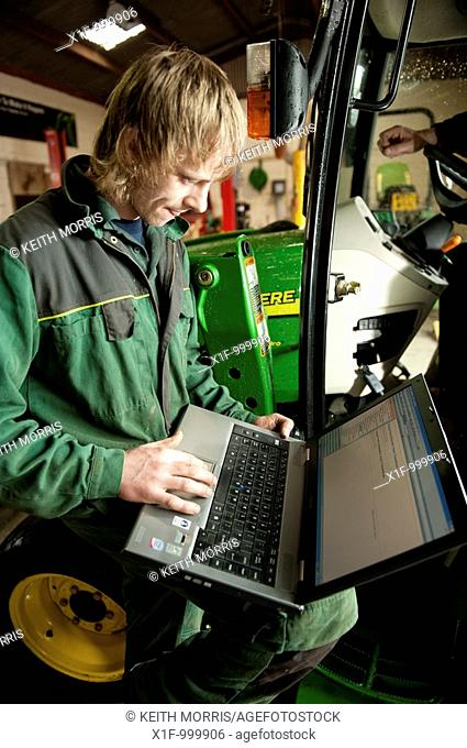 A young apprentice technician using computer technology to analyze the fault with a John Deere tractor on a garage workshop