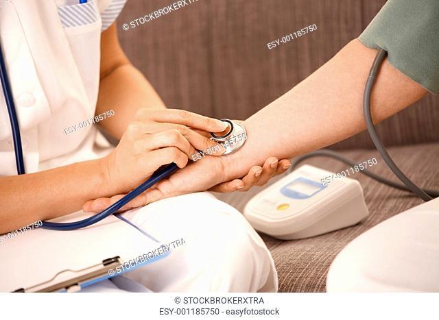 Close up of hand using stethoscope on wrist