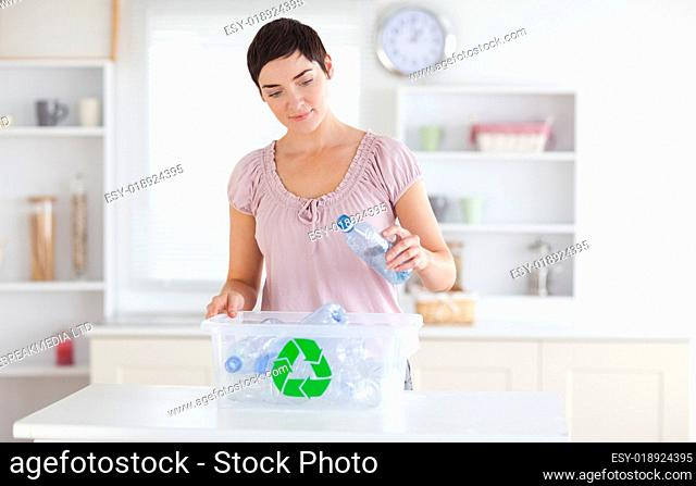 Woman putting bottles in a recycling box
