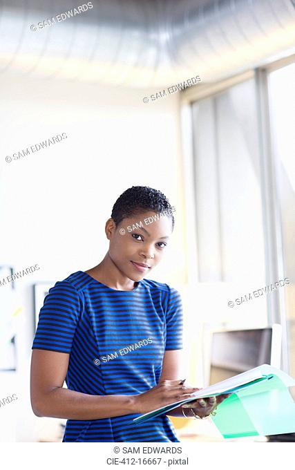 Portrait of confident businesswoman with paperwork